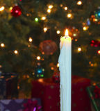 A White Christmas Candle with Blurred Lights Stock Photo