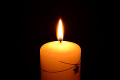 White christmas candle burning on a black background. Photo of a white christmas candle burning on a black background Royalty Free Stock Photography