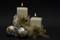 White Christmas candles and balls. Two white candles with a golden ribbon and some bright balls on a black background Royalty Free Stock Photo