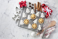 White Christmas Baking Cookies Background. Christmas cookies with xmas presents, spices and cookie cutters on a white marble background from overhead stock photo