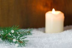 White Christmas decoration. Christmas decoration: branch of Christmas tree with white pearls and burning candle in snow Royalty Free Stock Image
