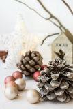White Christmas decoration composition, big pine cones, scattered baubles, shiny rattan star, wooden candle holder Royalty Free Stock Images