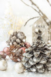 White Christmas decoration composition, pine cones, scattered baubles, shiny star, wooden candle holder, dry tree branches. Snow. royalty free stock images