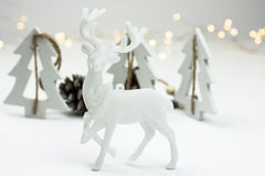 White Christmas decoration in scandinavian style with reindeer, wood fir trees and pine cones, bokeh lights in the background Royalty Free Stock Photo