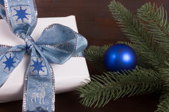 White Christmas gift with blue christmas ball on dark wooden background Stock Photo