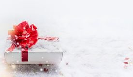 White Christmas gift box with red bow on snow with bokeh and snowfall, banner. royalty free stock image