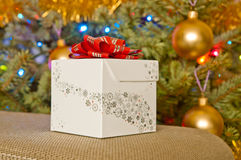 White Christmas gift next to a christmas tree Royalty Free Stock Photos