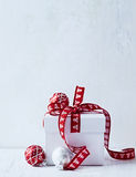 White Christmas gift with red ribbon. And Christmas ornaments Royalty Free Stock Photo