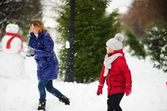 White Christmas. Girl plays with mother in snowballs in the winter park. Stock Photo