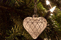 White christmas heart. White christmas ornament in heart shape hanging on a christmas tree Royalty Free Stock Photos