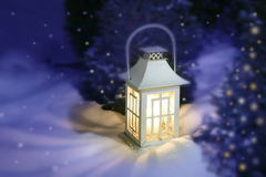 White Christmas lantern. In snow, with yellow candle light, on mysterious violet background stock photo