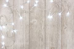 White Christmas lights corner border over light gray wood. White Christmas lights corner border, above view on a light gray wood background royalty free stock image