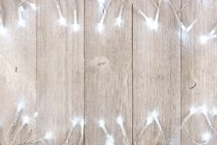 White Christmas lights double border over light gray wood. White Christmas lights double border, above view on a light gray wood background stock photo