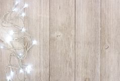 White Christmas lights side border over light gray wood. White Christmas lights side border, above view on a light gray wood background royalty free stock image