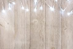 White Christmas lights top border over light gray wood. White Christmas lights top border, above view on a light gray wood background stock photo