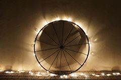 White Christmas lights on a wagon wheel. Small white Christmas light wrapped around a metal wagon wheel showing interesting light patterns on the side of the stock image