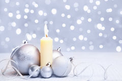 White Christmas ornament and candle. White or silver Christmas ornament and a candle with blur light background stock images