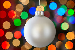 White Christmas Ornament Glowing Christmas Lights. White Christmas Ornament Over Colorful Multicolored Christmas Light Background Stock Photography