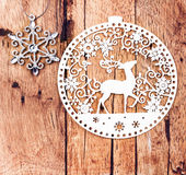 White Christmas Ornaments on rustic wooden board. Retro Christma. S star and lacy Deer Over Wood Background. Vintage style Stock Photo