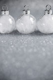 White christmas ornaments on silver glitter background with space for text. Stock Image
