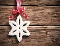 White Christmas snowflake on rustic wood. White Christmas snowflake decoration hanging from a fresh red and white ribbon and bow on rustic weathered wooden Stock Photography