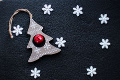 White Christmas snowflakes decoration and wooden Christmas toy on black textured background. Royalty Free Stock Photos