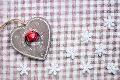 White christmas snowflakes and wooden heart decoration on checkered pink background. Vintage winter wallpaper. Top view Stock Photography