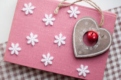 White christmas snowflakes and wooden heart decoration on pink background. Winter wallpaper. Top view Stock Image