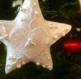 White Christmas Star. An embroidered white Christmas star hangs on the tree stock photo