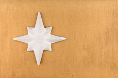 White Christmas star on gold background. Royalty Free Stock Images