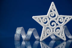White christmas star with silver ribbon on blue background with space for text Royalty Free Stock Photo