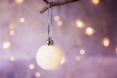 White Christmas Tree Ball Hanging on a Branch Golden Garland Glittering Lights in the background Festive Greeting Card. Poster Template Copy Space Royalty Free Stock Photography