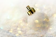White Christmas Tree Ball Lying in Bank of Snow Golden Pastel Color Garland Glittering Bokeh Lights Festive Magic Mood Stock Photos