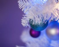 White Christmas tree with blue lights, white lights, turquoise ornament in front royalty free stock image