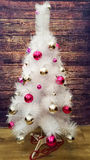 White Christmas tree decorated Christmas tree decorations silver and pink color. On wooden background Royalty Free Stock Images