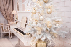 White Christmas tree decorated with golden ornament Stock Photos