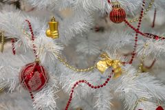 White Christmas tree decorated with yellow and red toys stock images
