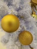 White Christmas tree decoration closed up glitter golden ball ornaments with white tinsel background Stock Photo