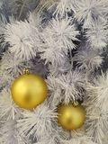 White Christmas tree decoration golden ball ornaments with white tinsel background. On the vertical Royalty Free Stock Image