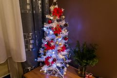White Christmas tree. Dressed Christmas tree with silver baubles and star flowers Royalty Free Stock Photography