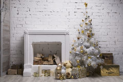 White Christmas tree with golden and silver balls, gift boxes, holiday decorations equipped fireplace. Brick wall background stock images