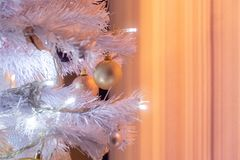 White Christmas tree illumination with ball glitter decoration. On blurred curtain royalty free stock photography