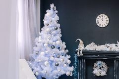 White Christmas tree near the fireplace stock photography