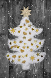White christmas tree of snow decorated with golden miniatures. Royalty Free Stock Images