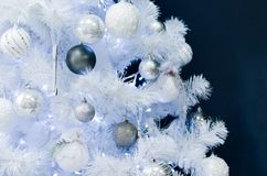 White Christmas tree with toys on the black wall. stock photos