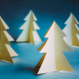 White Christmas Trees Made Of Old Paper On Blue Stock Photos