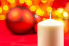 White christmas wax candle and balls on red background Stock Photography