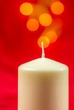 White christmas wax candle on red background Stock Photos