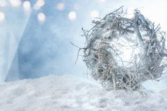 White christmas wreath in the snow. White christmas wreath and a lights string in the snow with bright silver bokeh for a winter decoration stock photography
