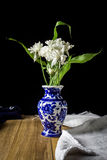 White chrysanthemum flower in blue vase still life on wood board. With fabric stock image